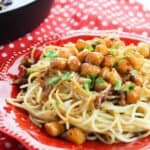 A red dinner plate topped with scallops pasta with a brown butter.