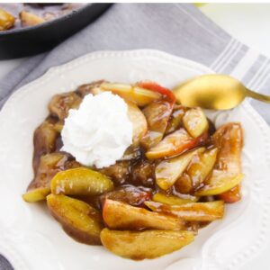 Fried Apples in a white bowl topped with fresh whipped cream.