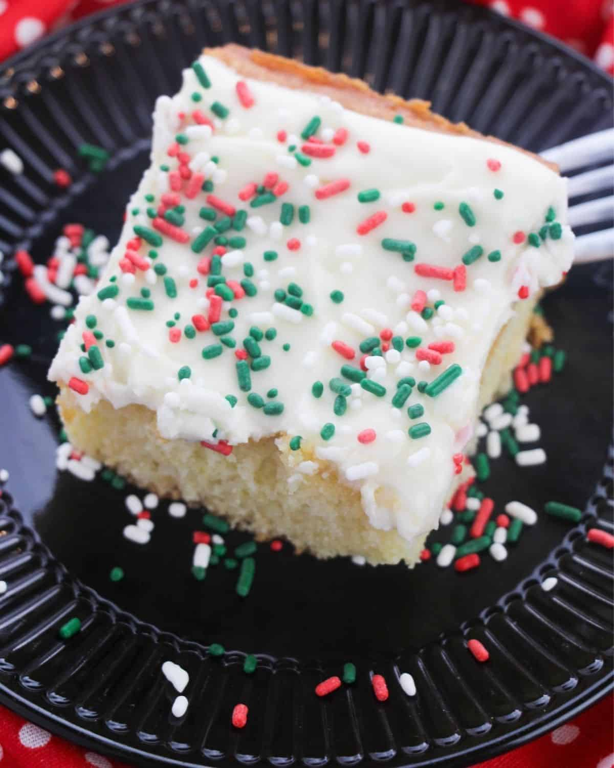 A slice of sugar cookie cake topped with white cream cheese frosting and sprinkles on a black plat