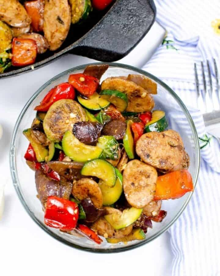 A cast iron skillet with sausage and veggies and a bowl in front of the skillet with a serving of the sausages. A fork is to the right of the bowl.