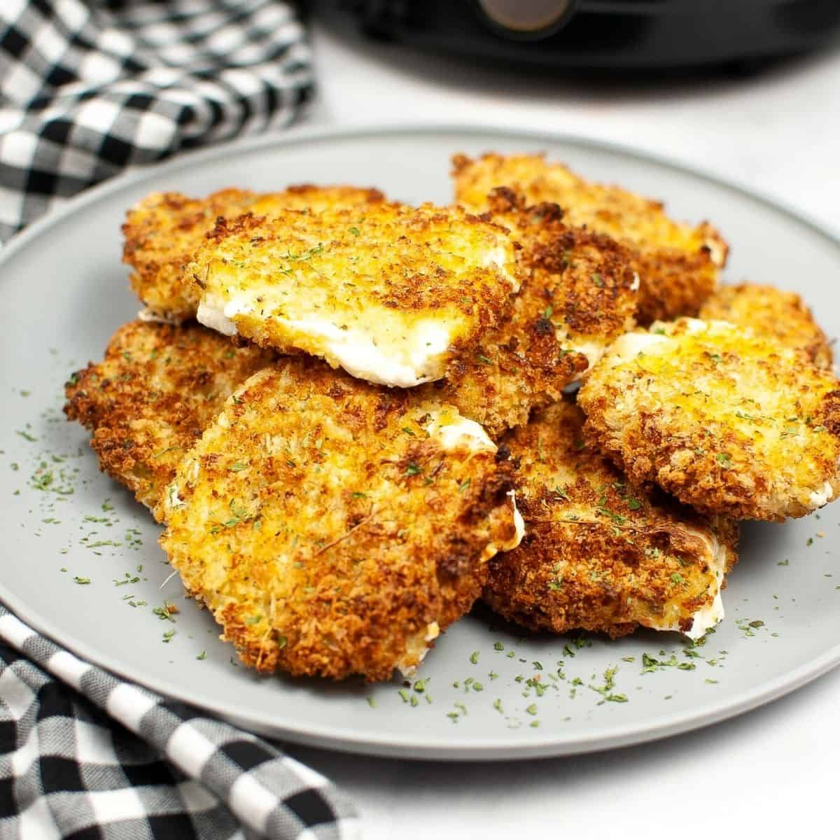 Sliced mozzarella coated with Panko bread crumbs on a grey plate.
