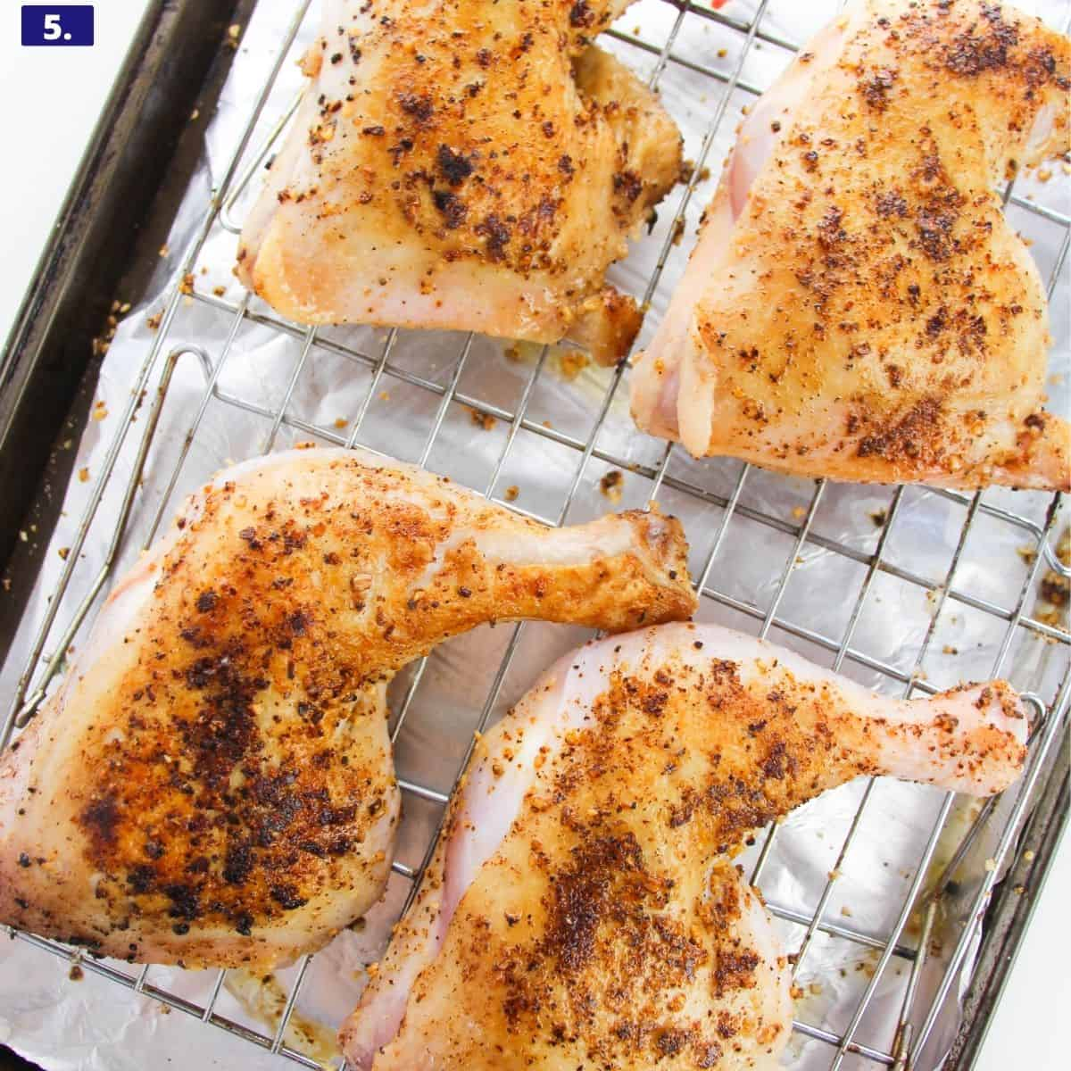 chicken quarters with spice rub on a baking sheet ready to be baked