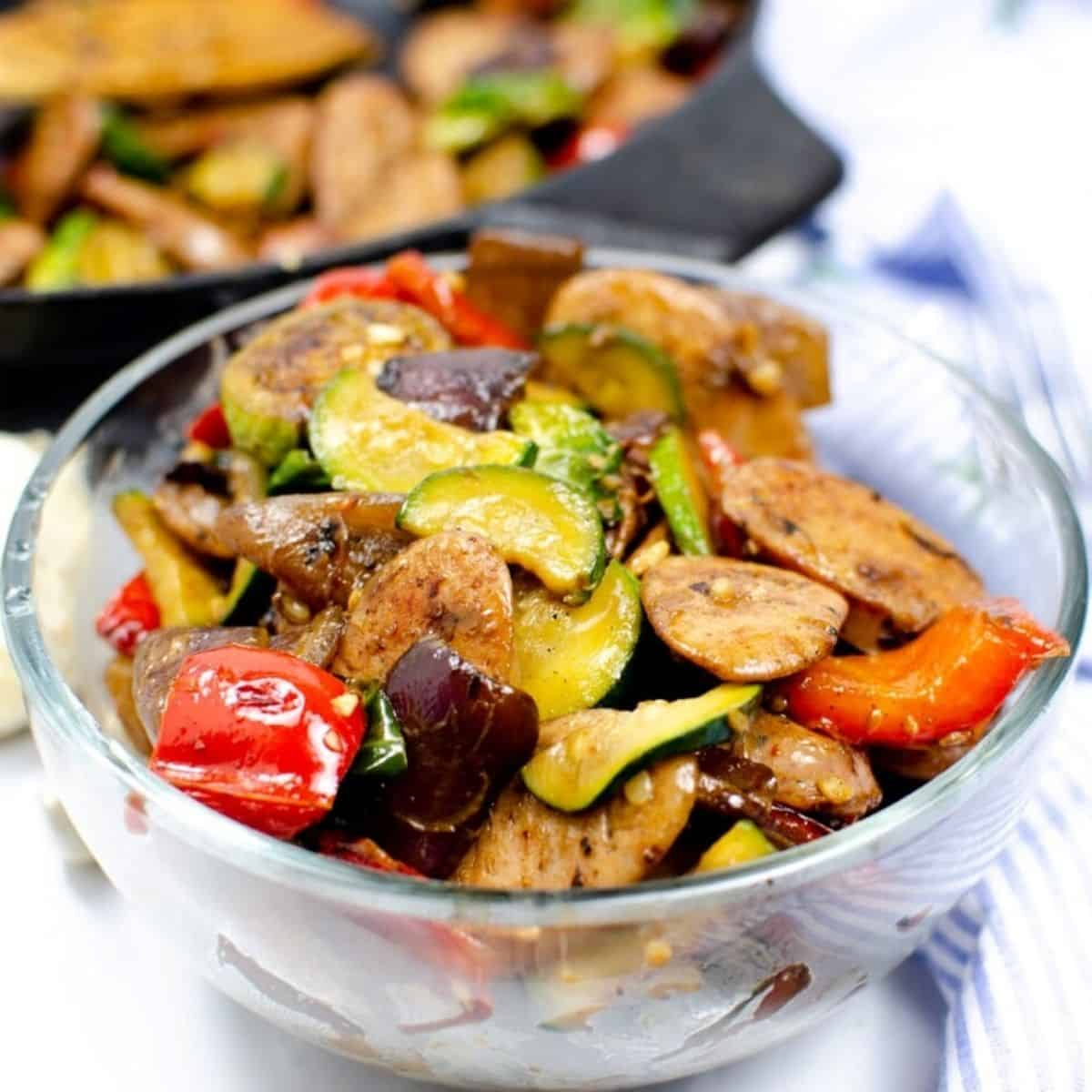 A bowl filled with sautéed vegetables and sliced chicken sausage.