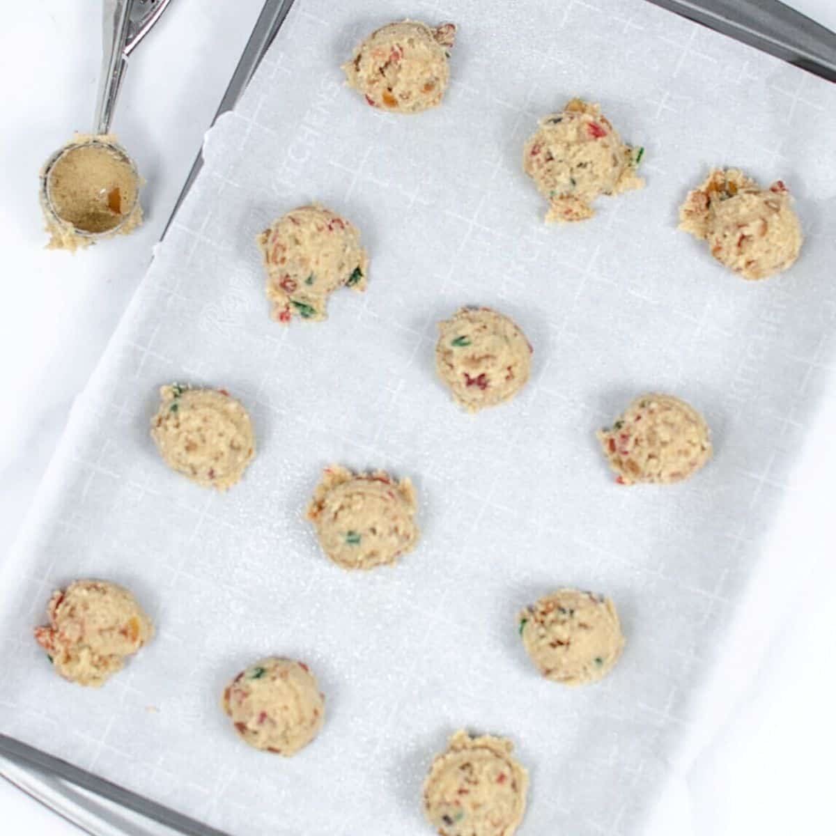 Fruitcake cookie dough balls on a cookie tray lined with parchment paper.