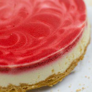 red velvet swirl cheesecake on a white plate.