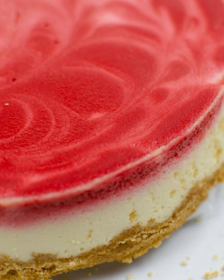 red velvet swirl cheesecake on a white plate.