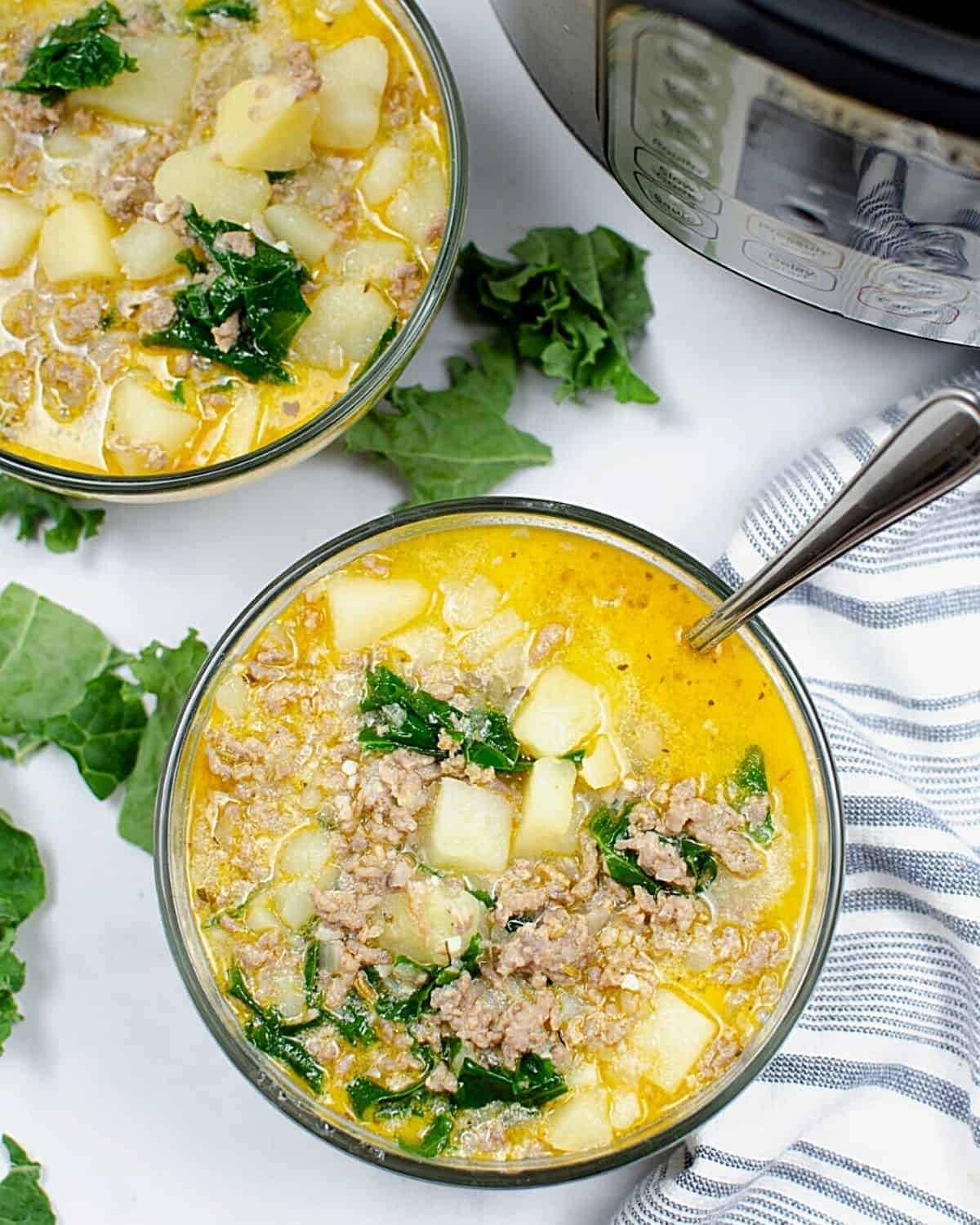 Two bowls of soup loaded with potatoes, kale, and ground sausage next to an Instant Pot