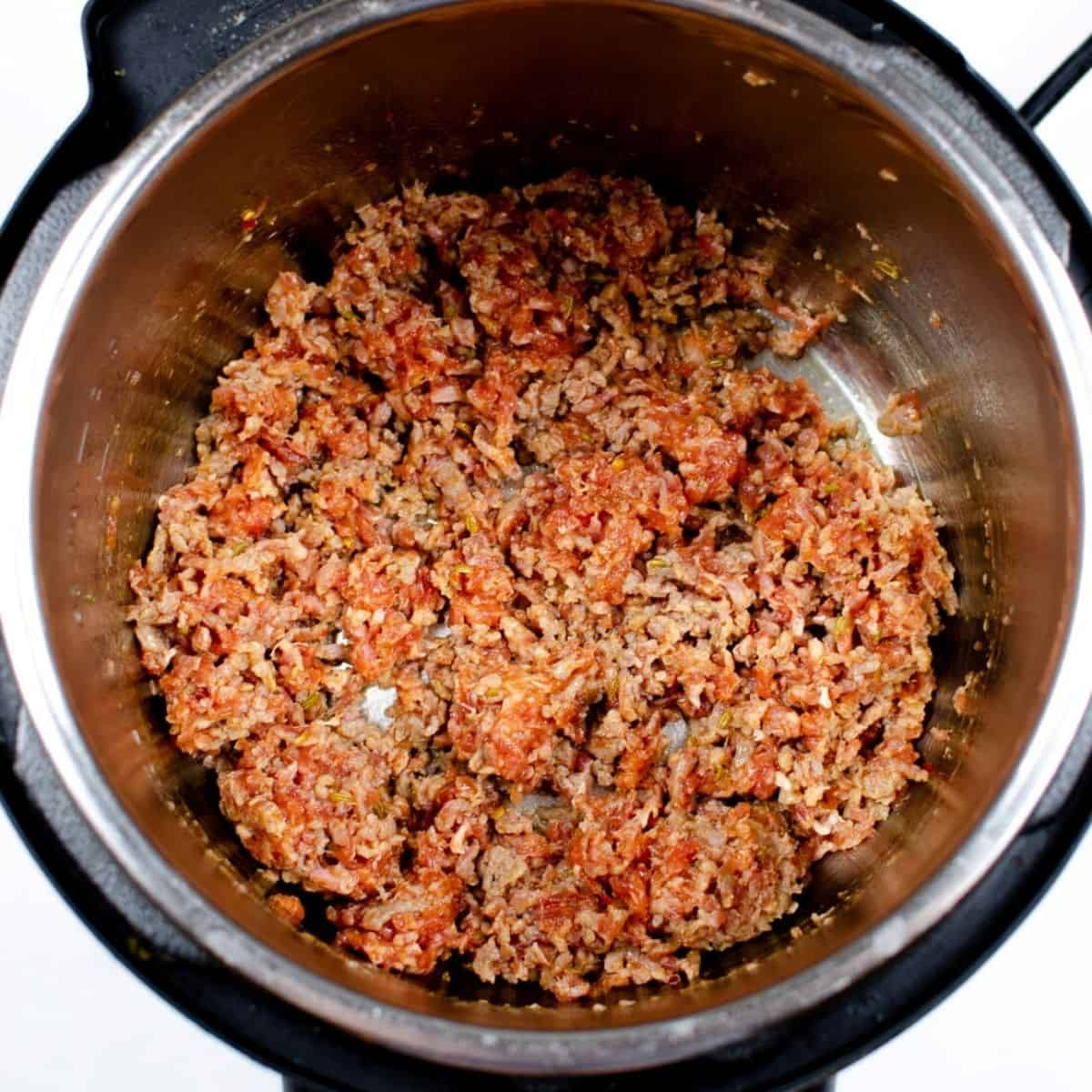 Ground sausage meat browning in an Instant Pot.