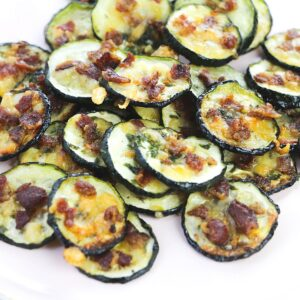 A pile of baked zucchini slices topped with bacon and cheese on a white plate.