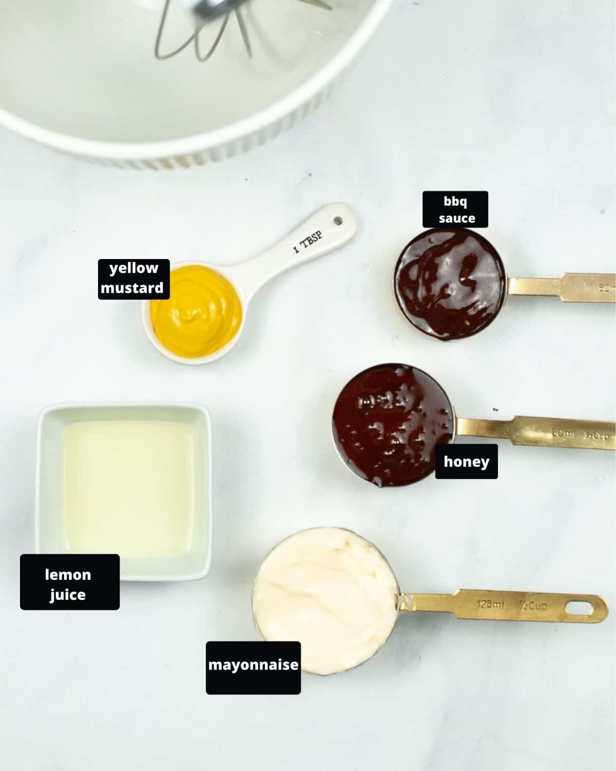 Honey, bbq sauce, yellow mustard, lemon juice, and mayonnaise in measuring spoons.