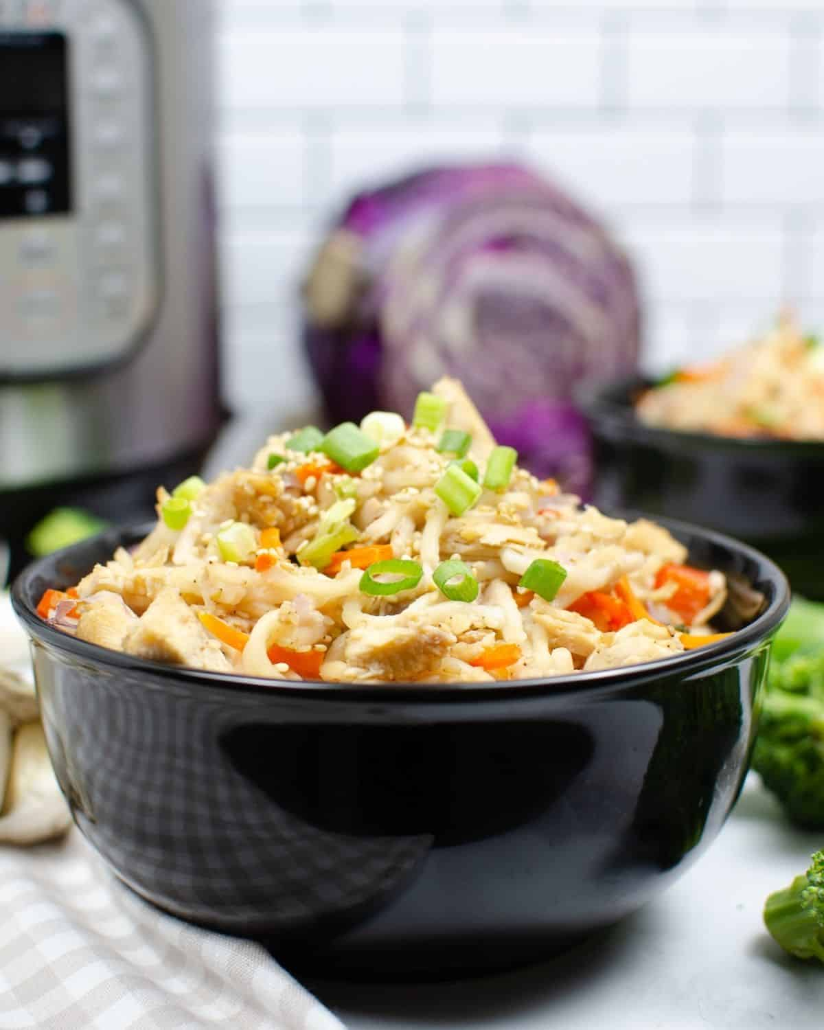 A bowl of noodles and veggies topped with green onions in a black bowl in front of an instant pot.