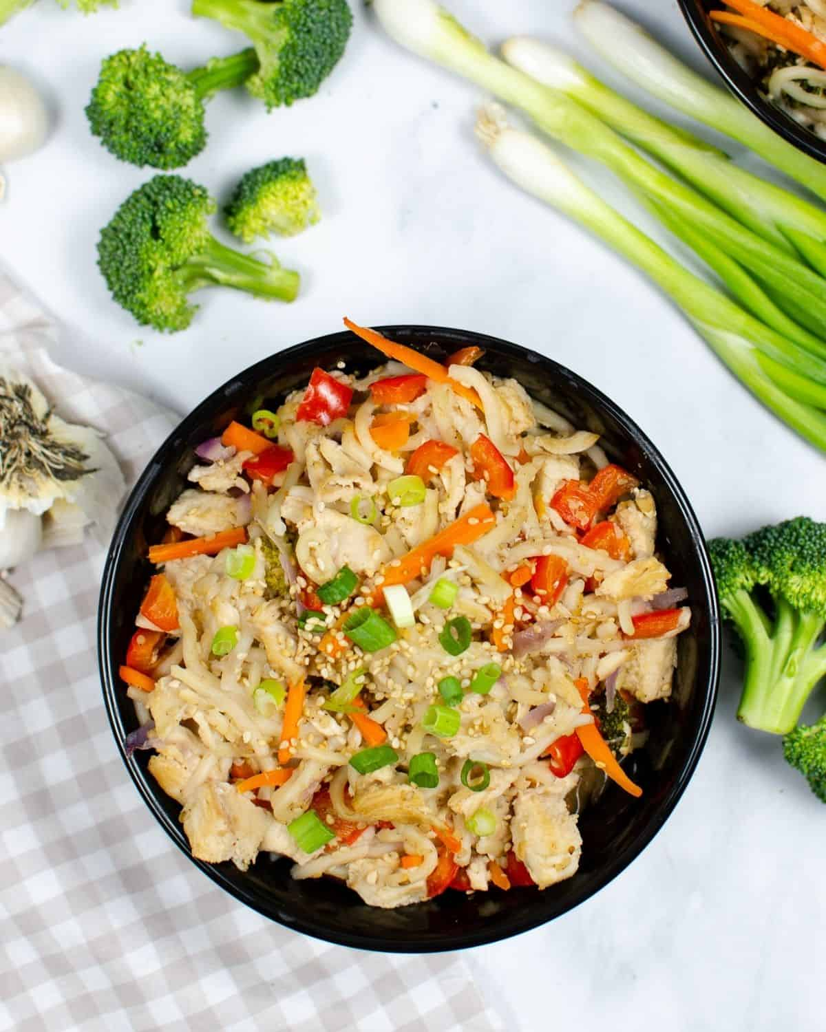 An overhead view of chicken chow mein in a black bowl with veggies around the bowl