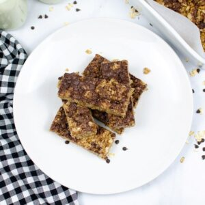Homemade granola bars stacked on a white plate with a checkerboard napkin next to the plate.