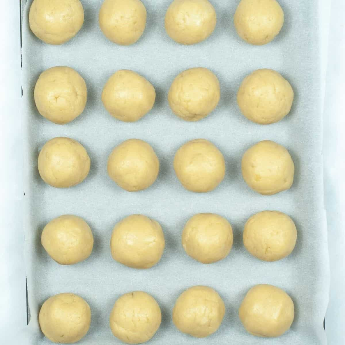 Rolled cake pop dough on a baking sheet lined with parchment paper.