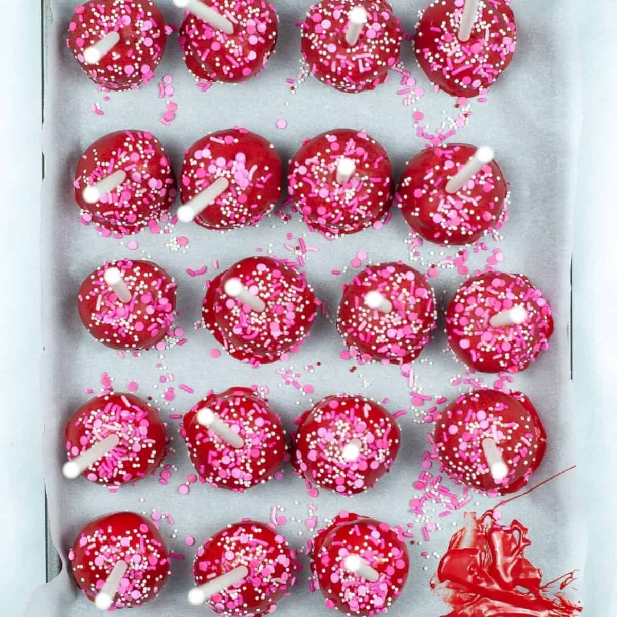 A sheet pan with red cake pops with pink sprinkles with cake