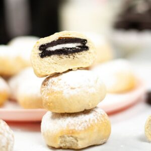 Three fried Oreos stacked together with the top one sliced in half.