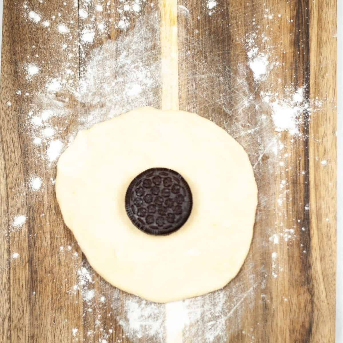Biscuit dough on a cutting board with an Oreo in the middle of the dough.