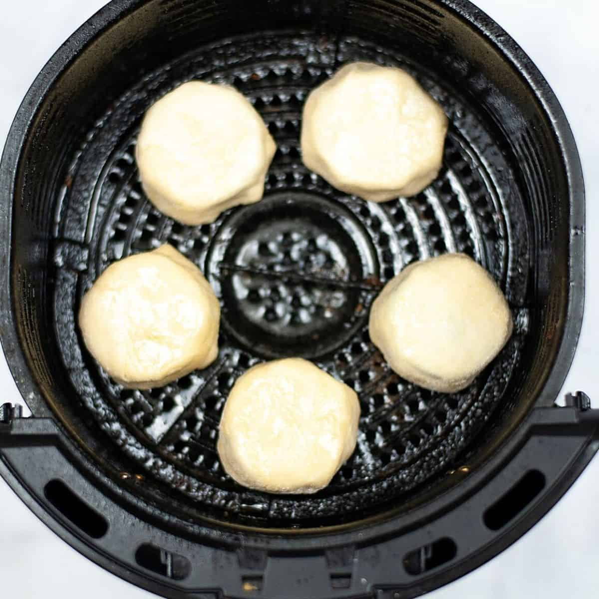 An overhead view of biscuit wrapped Oreos in an air fryer.