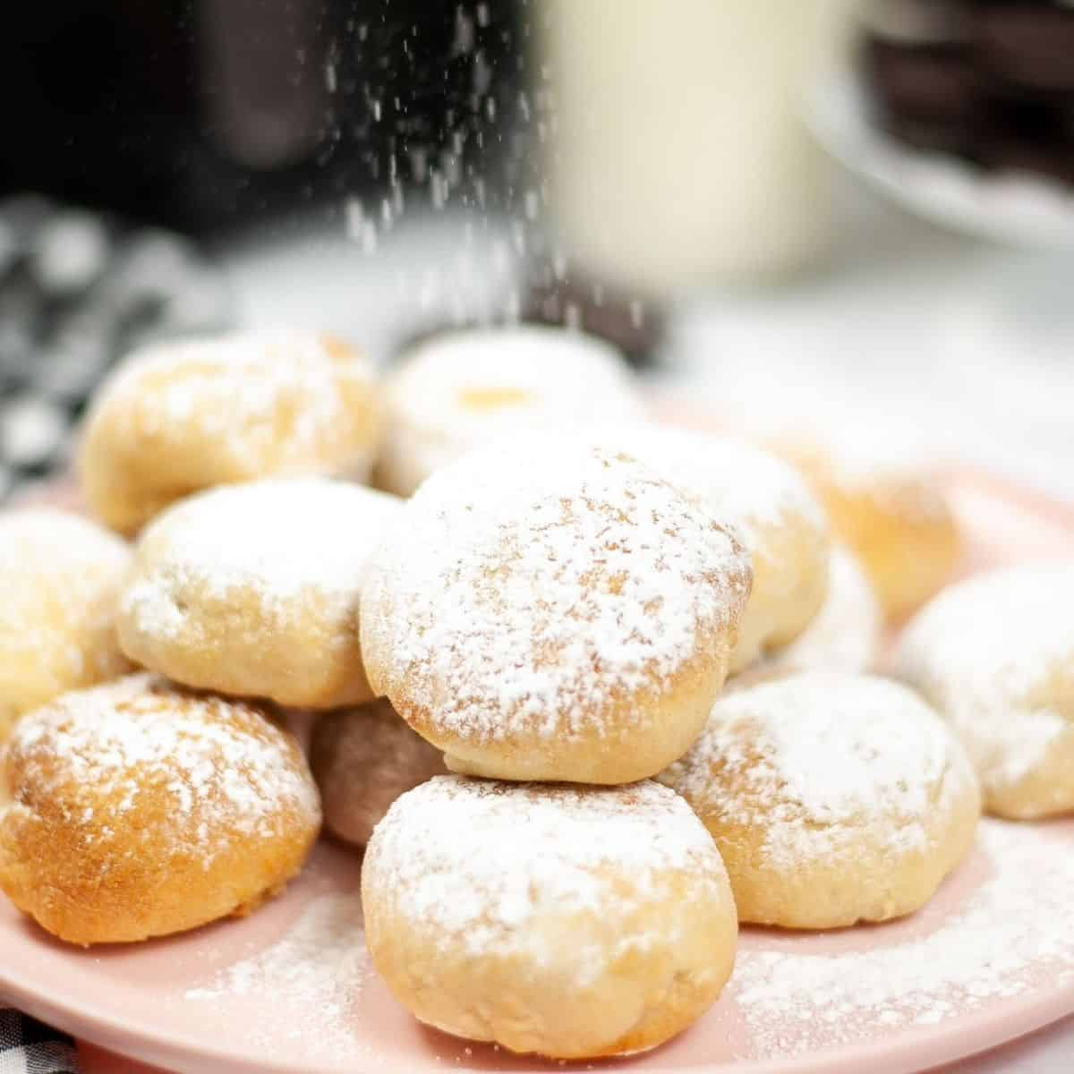 Oreos that have been wrapped in biscuit dough and air fried being dusted with powdered sugar.