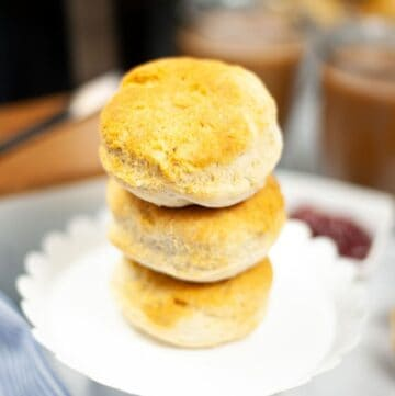 Homemade biscuits stacked up on a white cake stand.