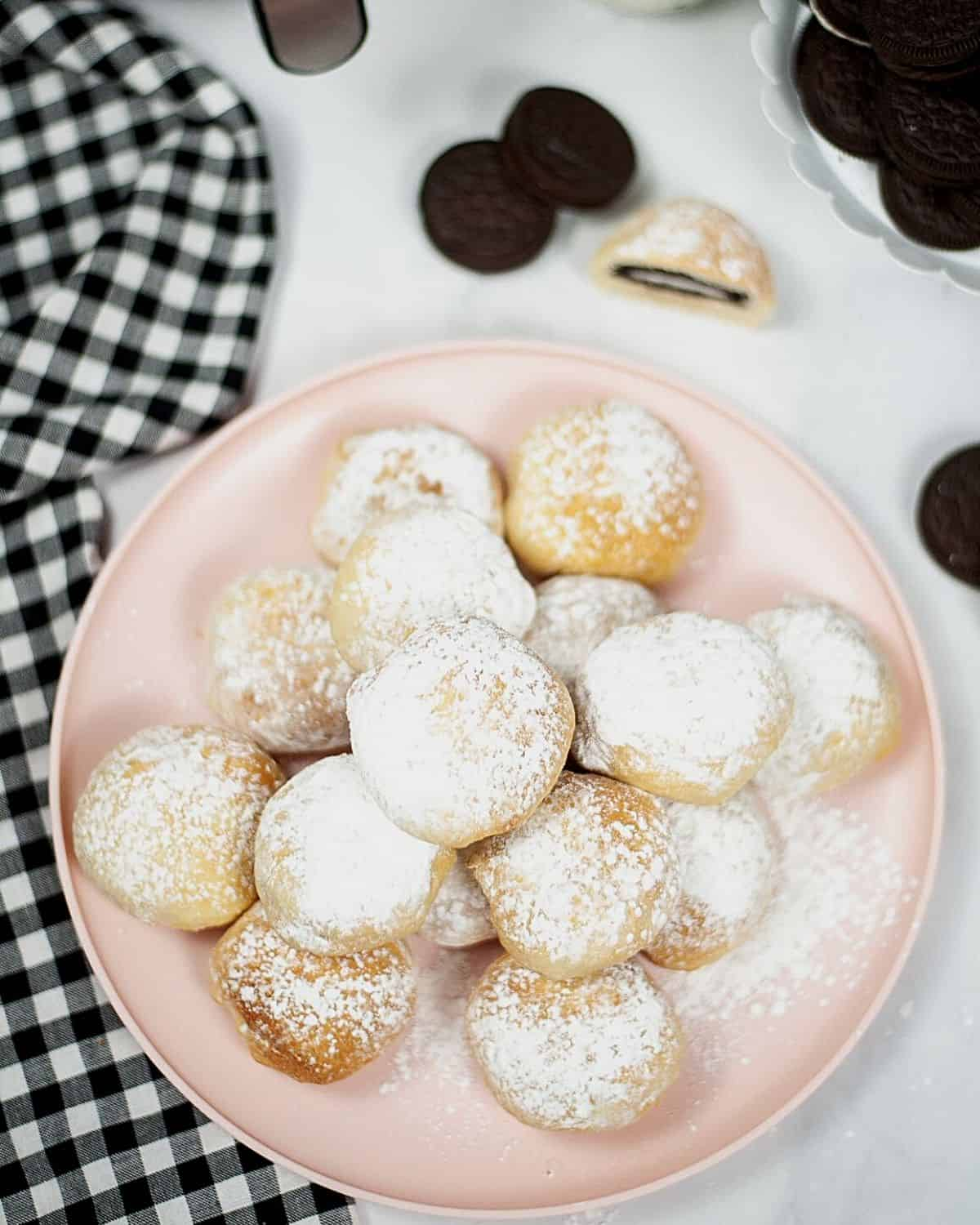 An overhead view of fried Oreos on a pink plate.