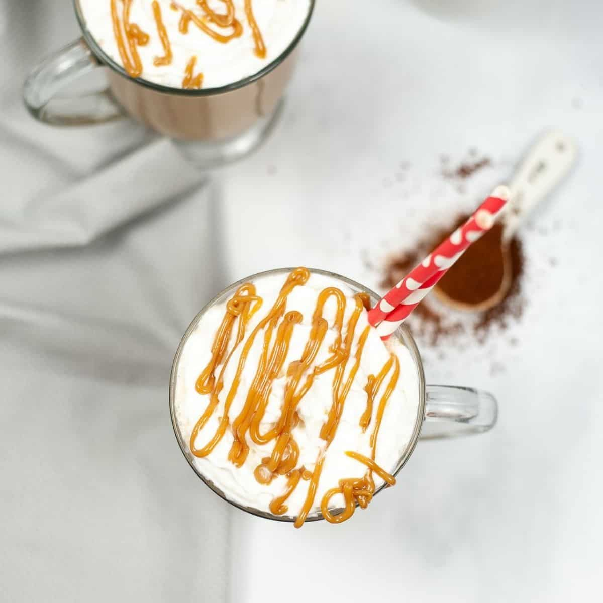 An overhead shot of two mugs of caramel macchiato topped with whipped cream, caramel sauce, and a straw in the cup.