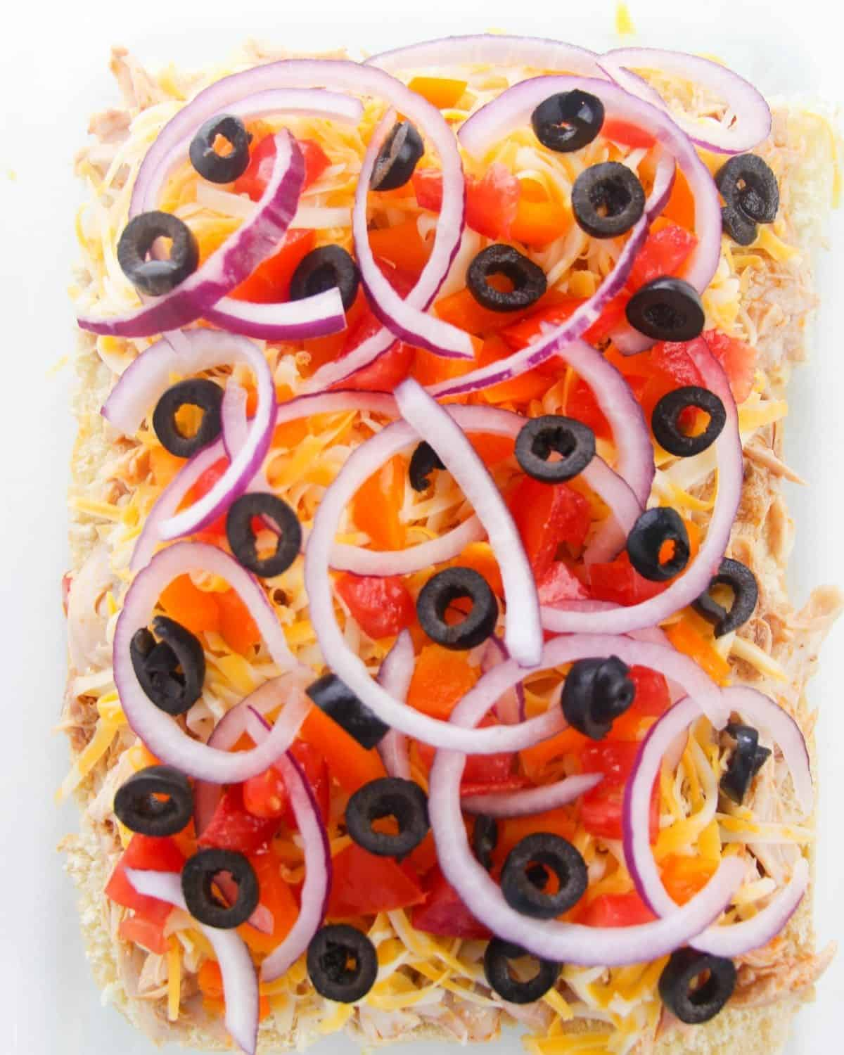 Layers of shredded cheese, red onions and diced olives