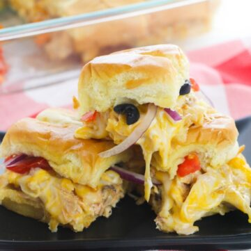 A stack of sliders filled with cheese, chicken. olives, and onions