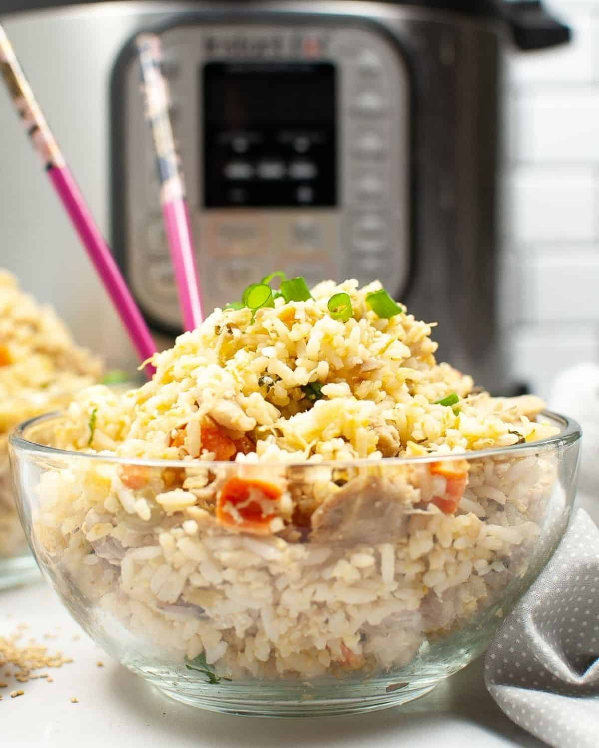 A glass bowl of fried rice, chicken , and veggies in front of an Instant Pot