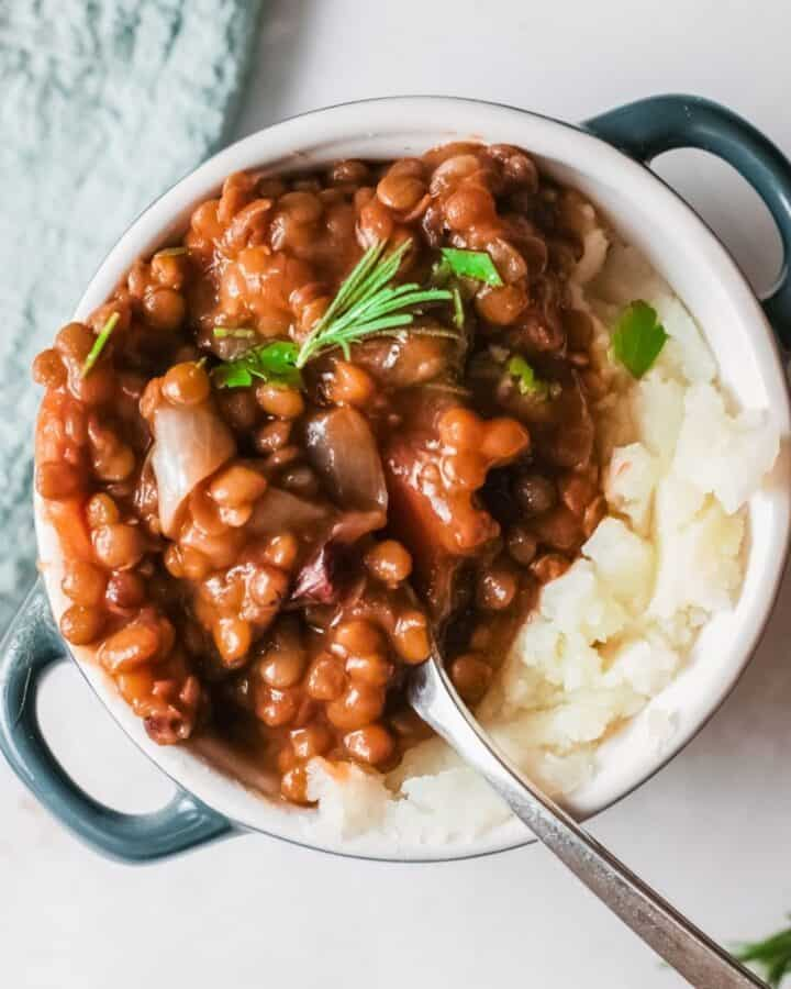 A blue pot with mashed potatoes and lentil stew