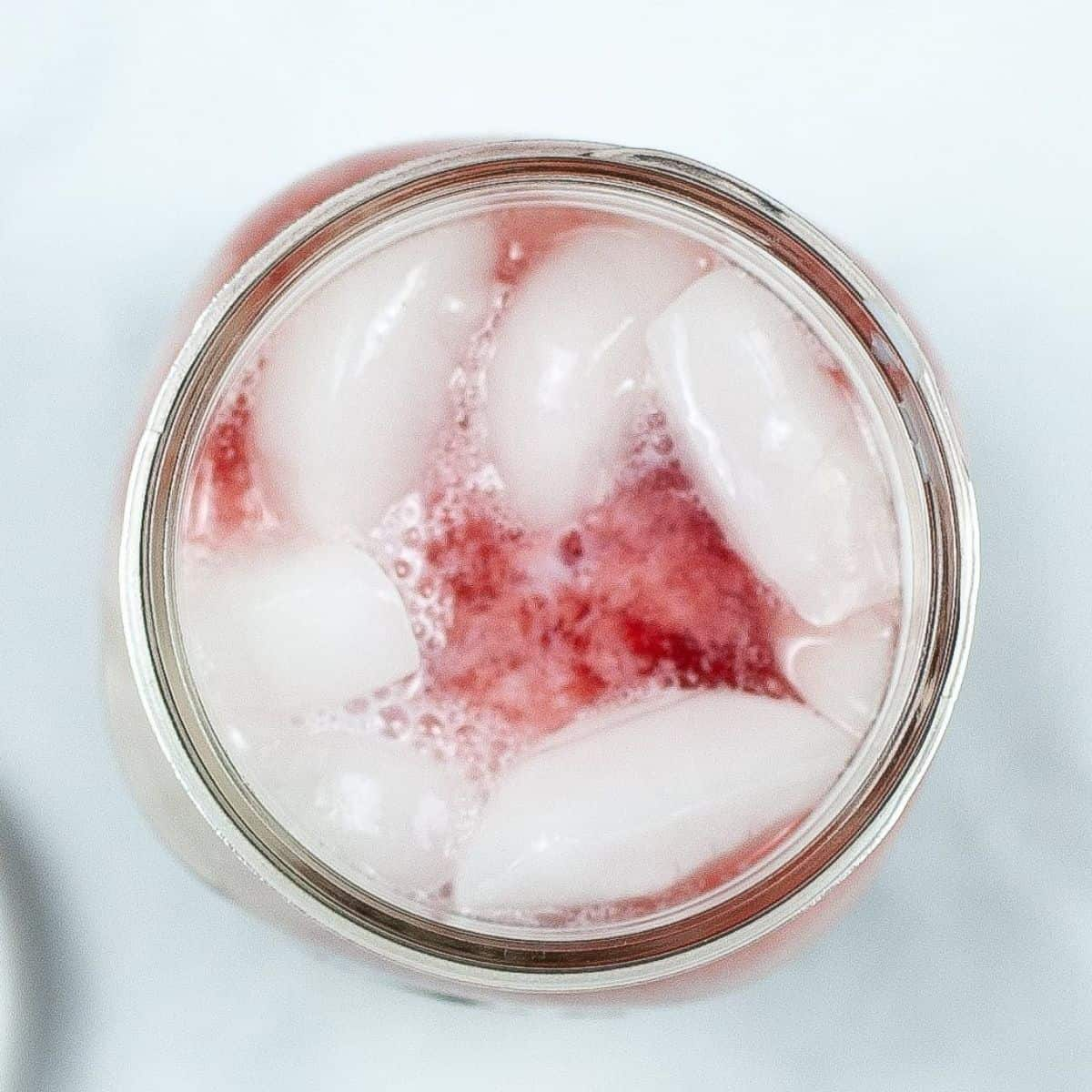 An overhead view of a mason jar with ice and pink tea.