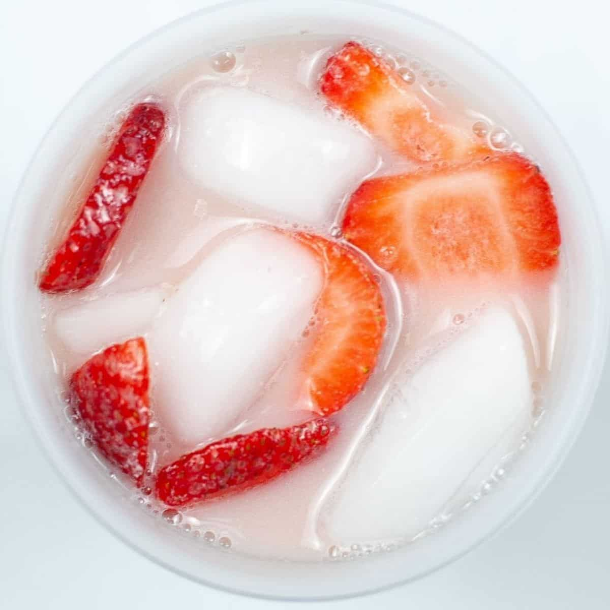 An overhead view of a cup with ice, strawberries, and pink drink.