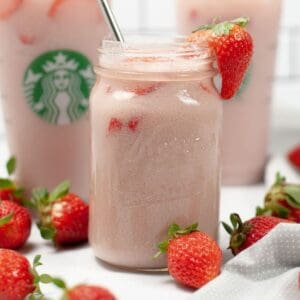A clear glass mason jar filled with a pink drink copycat drink with a silver straw and a strawberry on the edge of the glass.
