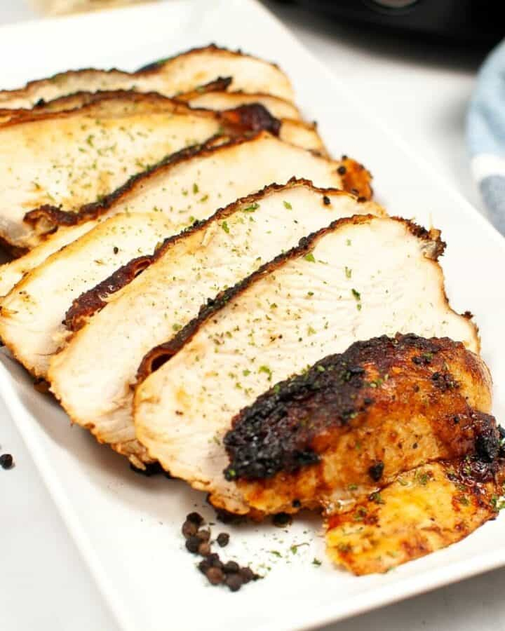 Sliced turkey on a plate with a golden crust.