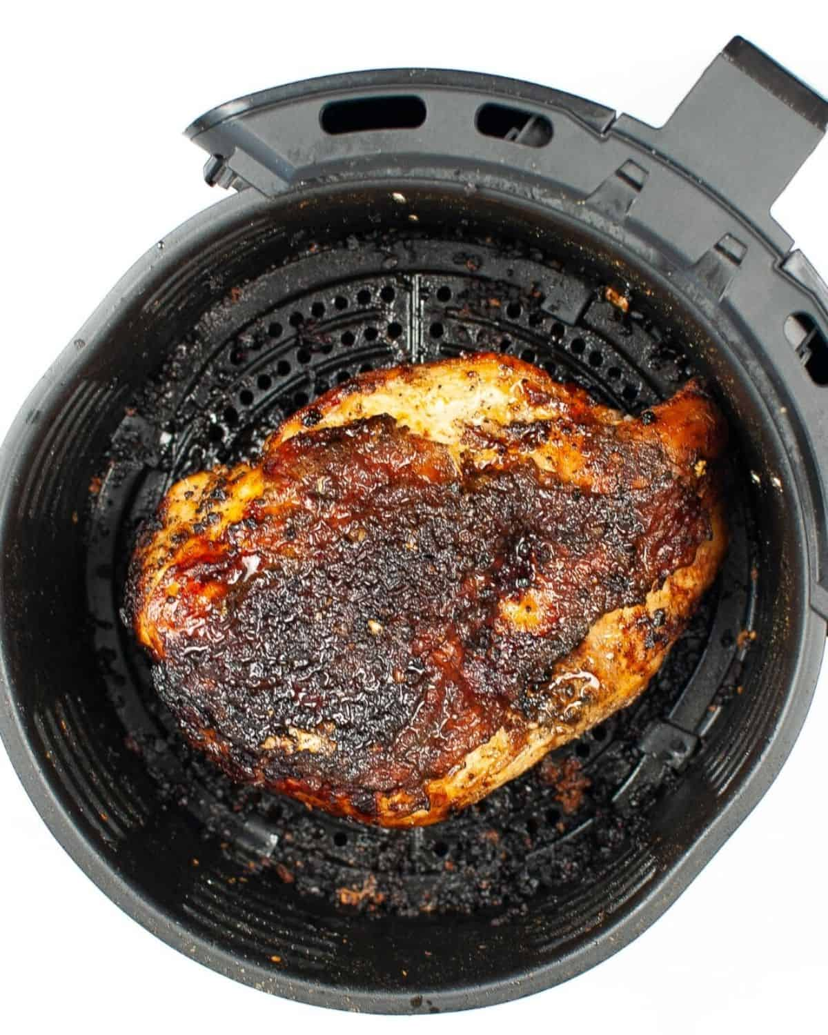 A cooked turkey in the air fryer with crispy brown golden skin.