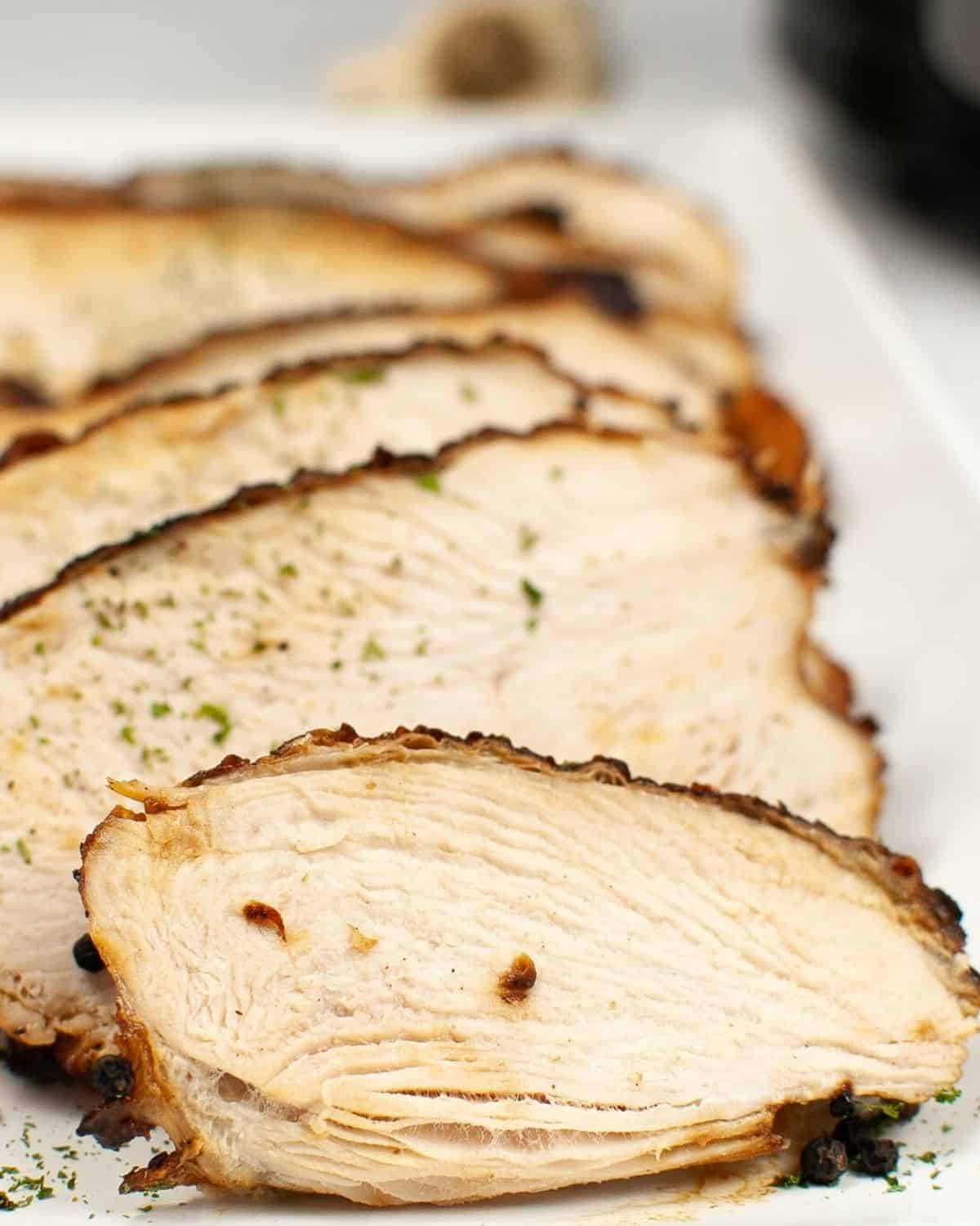 Turkey breast that has been cooked and sliced with a sprinkle of parsley on a white plate.