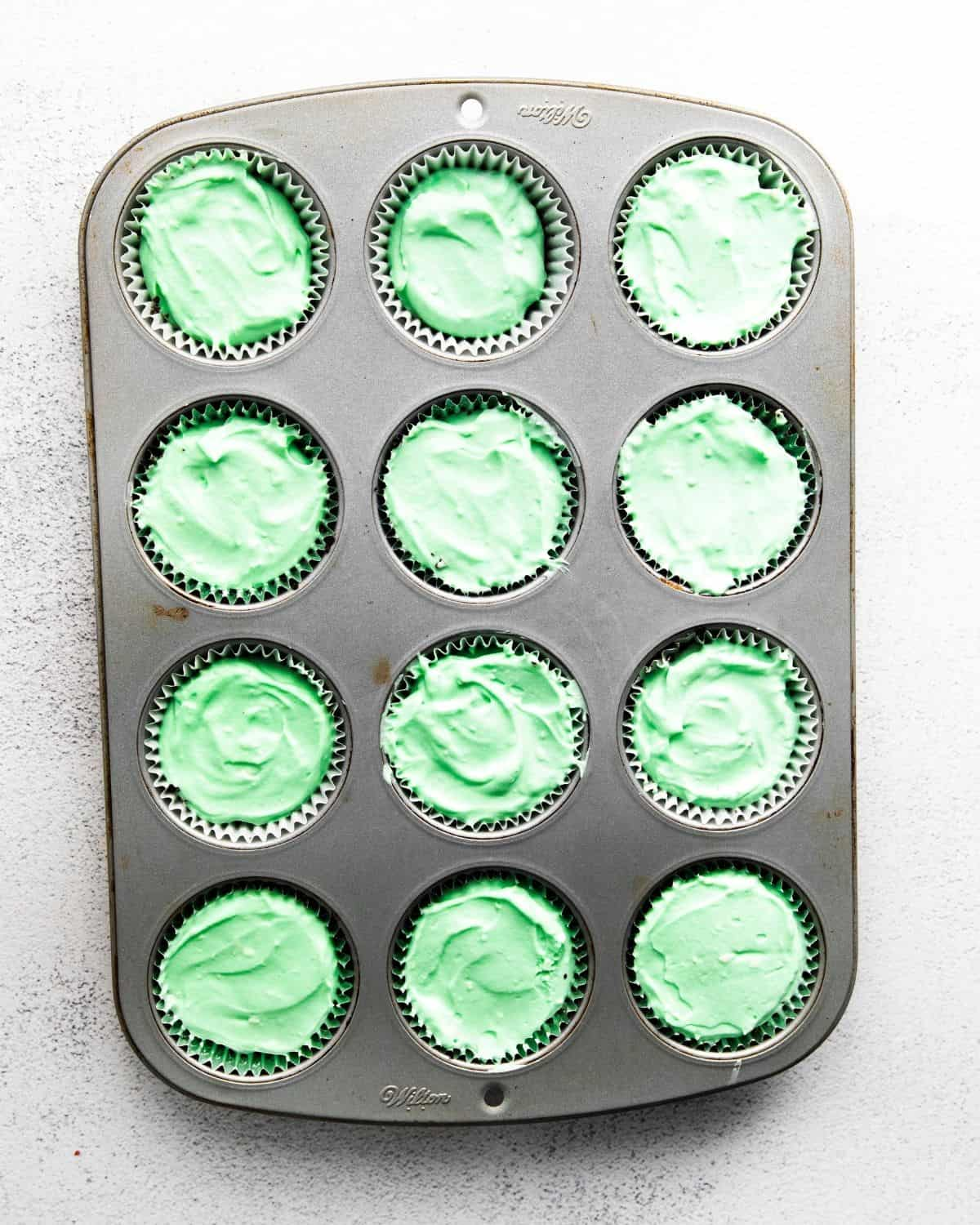 A 12 count muffin tin with green cream cheese in each tmold.