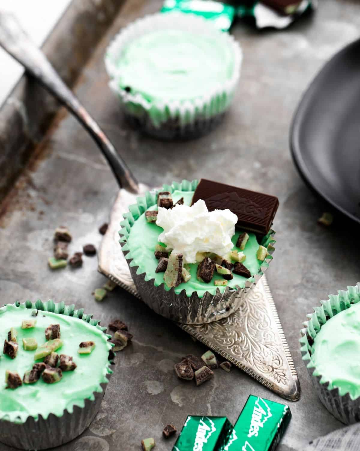 A grey platter with a few mini cheesecakes in cupcake liners. In the middle of the photo is a silver serving spoon with a whipped cream and mint decorated mini cheesecake in an aluminum foil cupcake liner.
