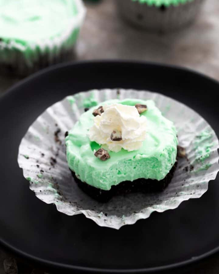 A mini cheesecake with an Oreo bottom and green tinted cream cheese topped with whip cream and chopped mints on an open cupcake liner.
