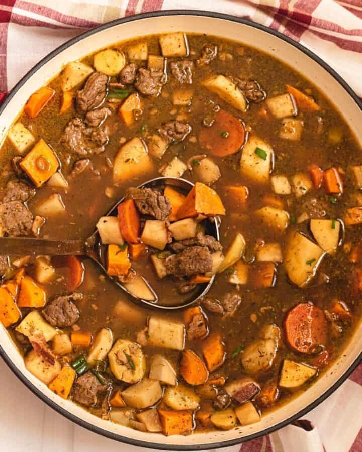 A large Braiser pot filled with veggies and beef in a dark brown broth.
