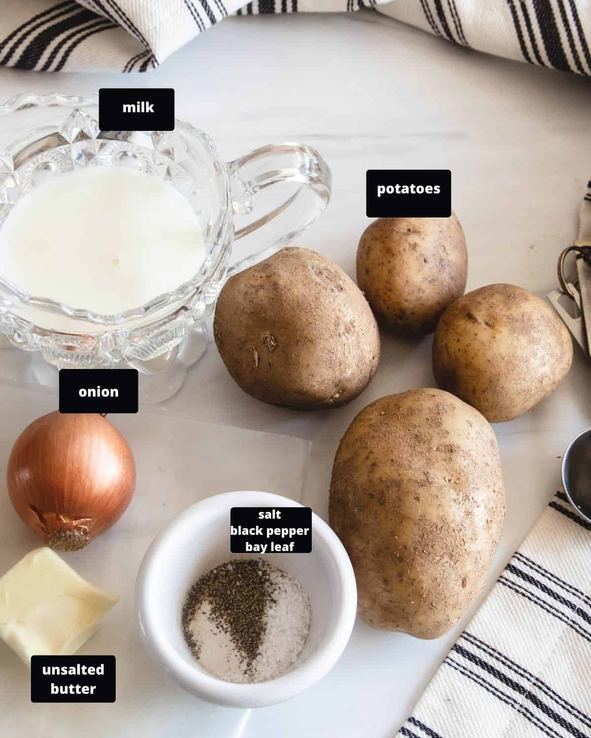 Ingredients to make homemade mashed potatoes - russet potatoes, milk, onion, butter, black pepper, and salt.