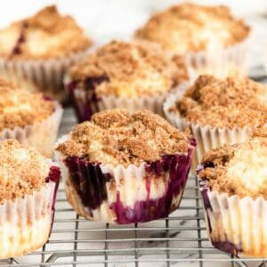 Streusel topped blueberry muffin sin a cupcake liners on a silver wire wrack.