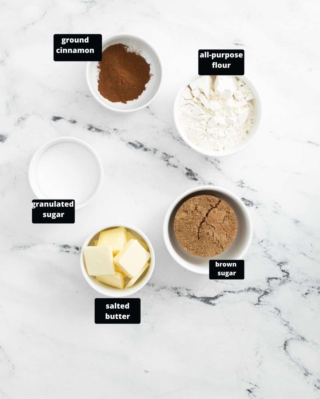 Ground cinnamon, all-purpose flour, sugar, butter, and brown sugar in white bowls.