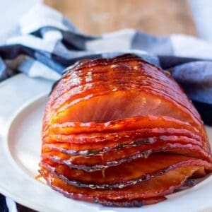 A sliced glazed ham on a plate with a blue and white checkered napkin behind it.