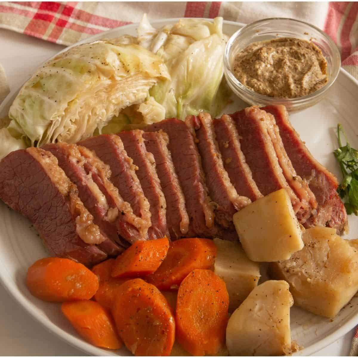 Sliced corned beef and cabbage with carrots and potatoes on a white plate.