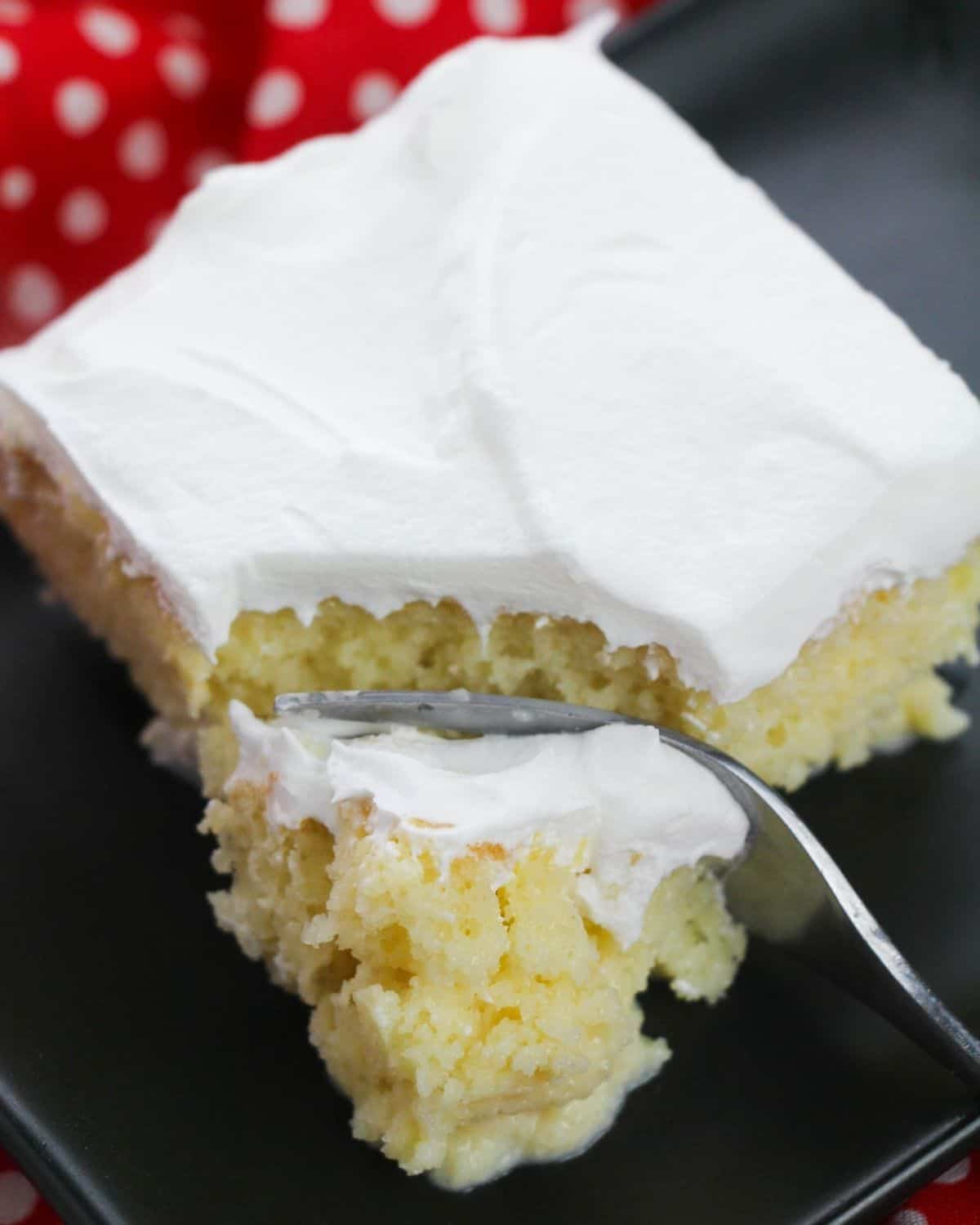 A slice of cake with a whipped cream frosting on a black plate.
