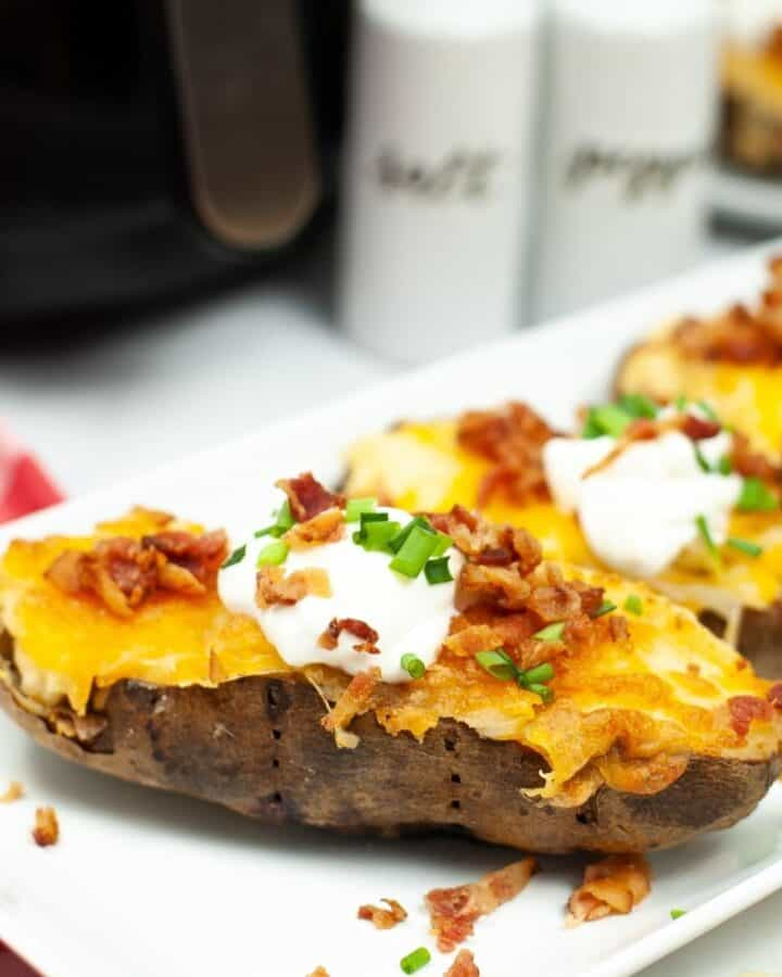 A side view of a potatoes on a white plate topped with cheese, bacon, sour cream, and chopped scallions.
