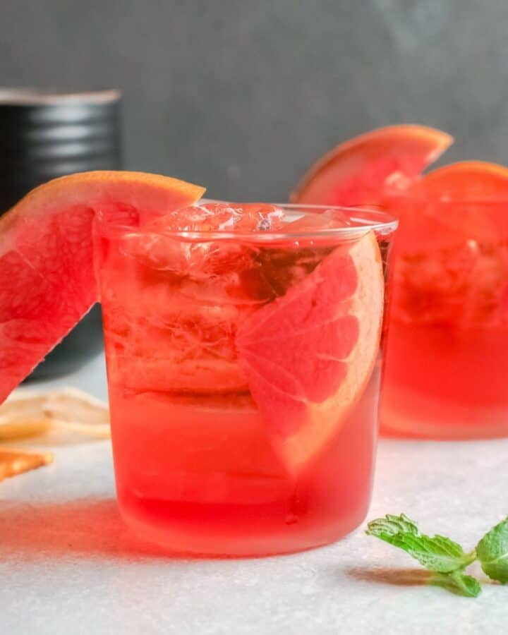 2 clear glasses filled with ice, aperol liquor and a wedge of fruit in the glass.