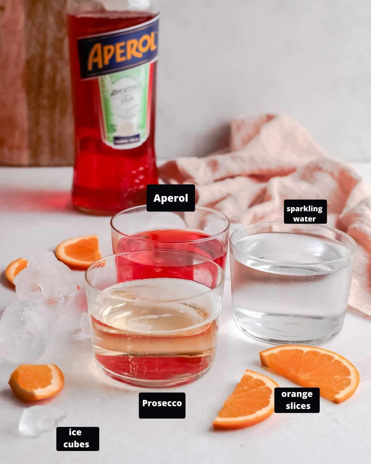 Ingredients to make aperol spritz, aperol, sparkling water, and proecco.