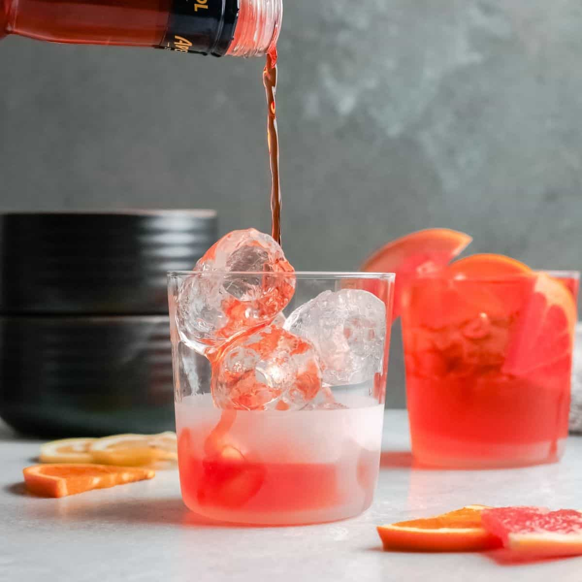 Aperol liquor being poured into a clear glass filled with ice.